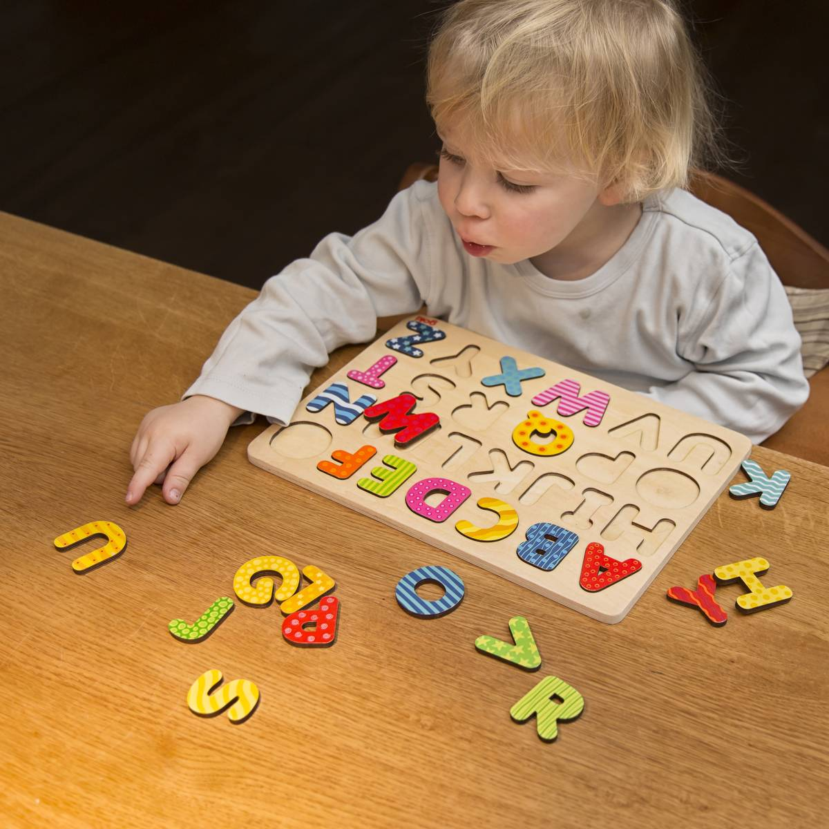 Boy, 2 years old, playing with an ABC puzzle