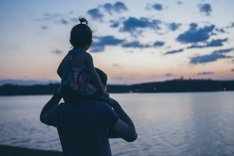 dad holding small child on his shoulders while staring out at pretty lake view