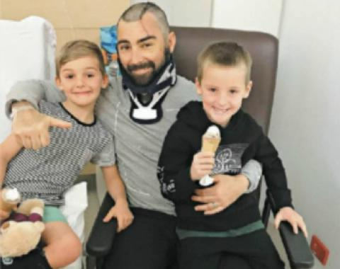 brad lewis posing with his two sons at the hospital