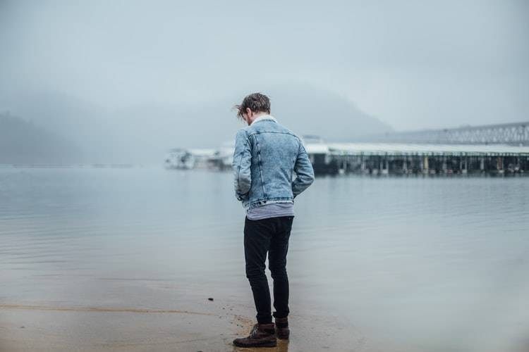 back shot of man in jean jacket on beach looking down at the ground