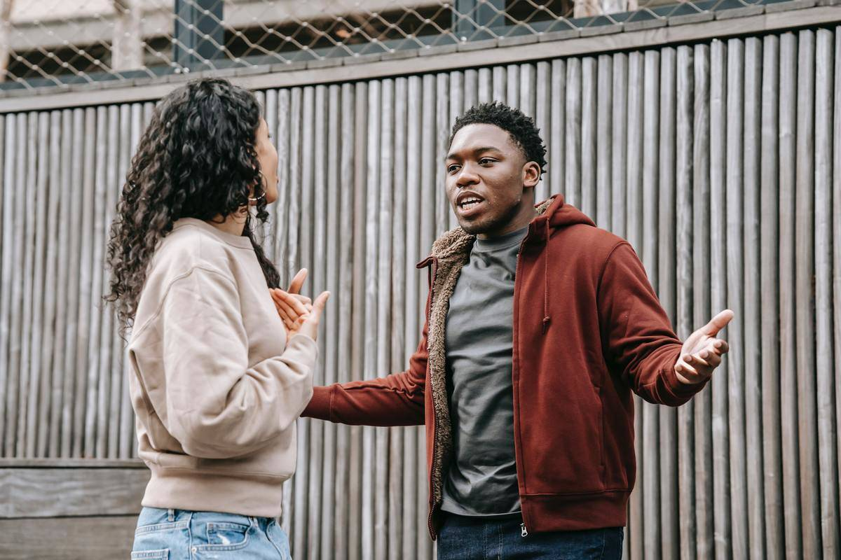 Mans hands outstretched while couple have disagreement