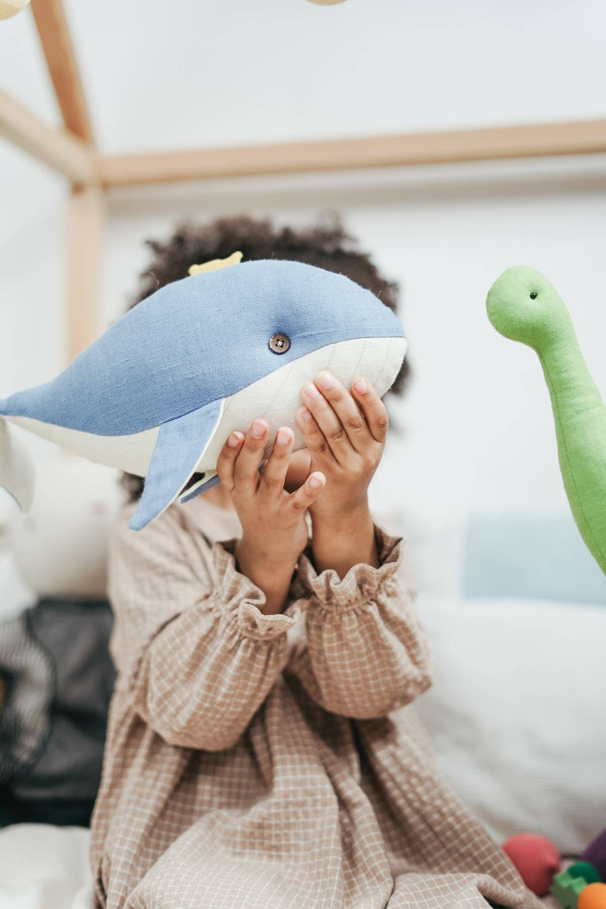 Small child holds stuffed whale toy in front of face
