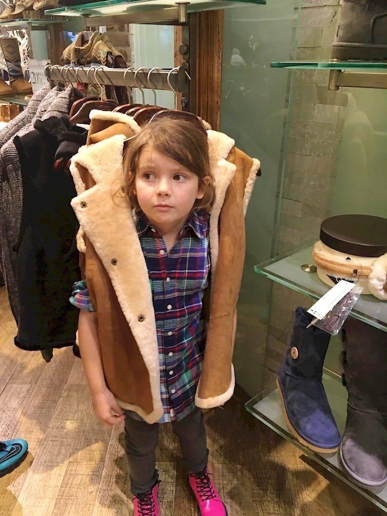 kid in vest hanging on rack