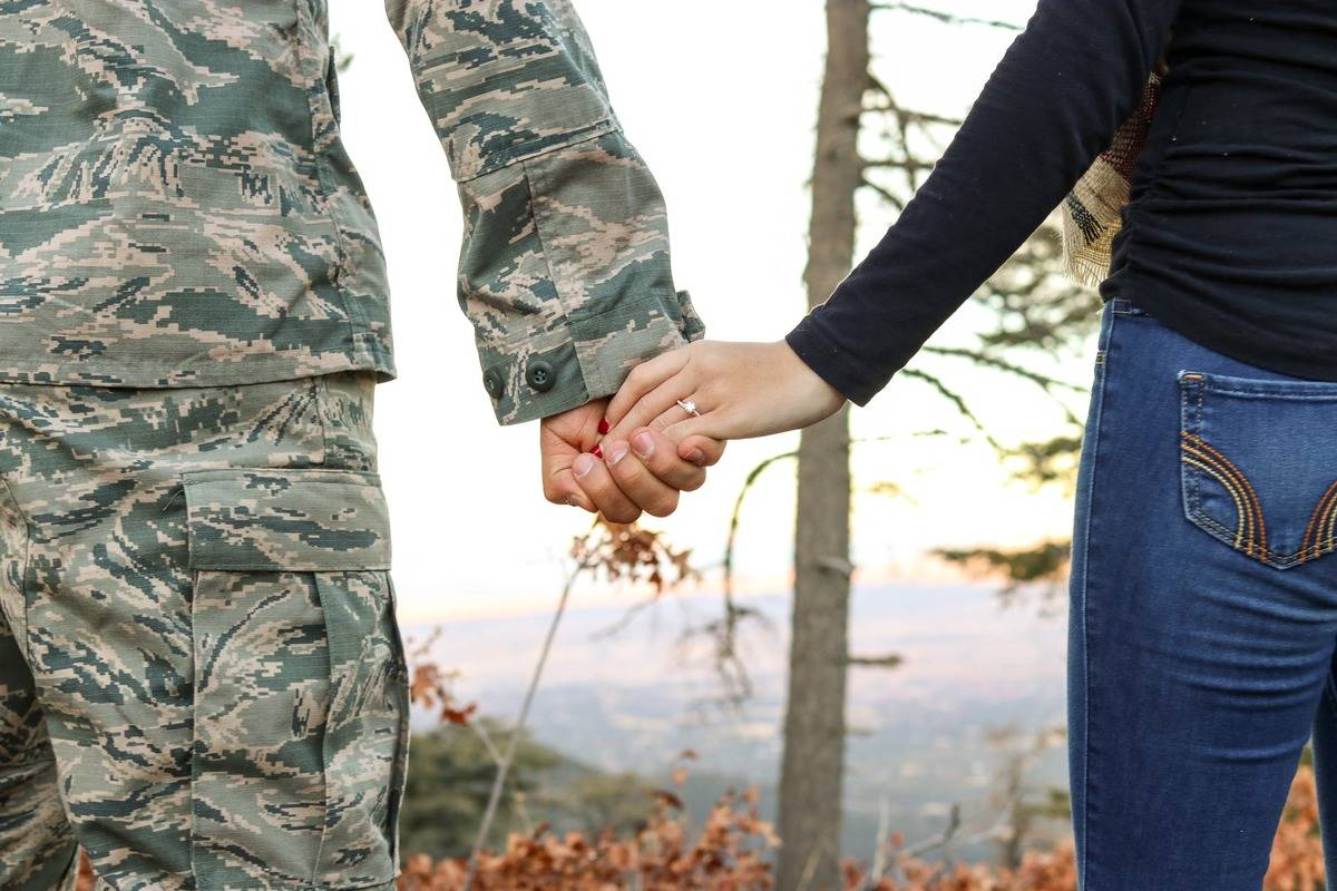 man in army fatigues holding hands with woman in jeans