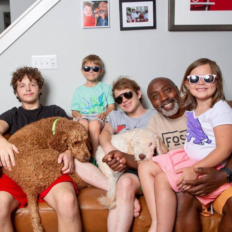 Man, four kids, and two dogs, sit on couch together, 3 kids wear sunglasses