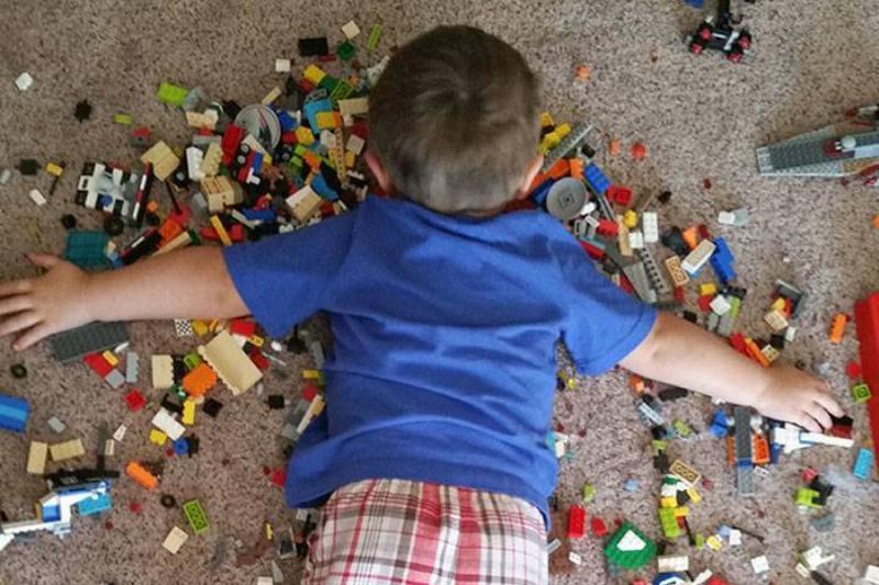 Boy lying face-down on Lego