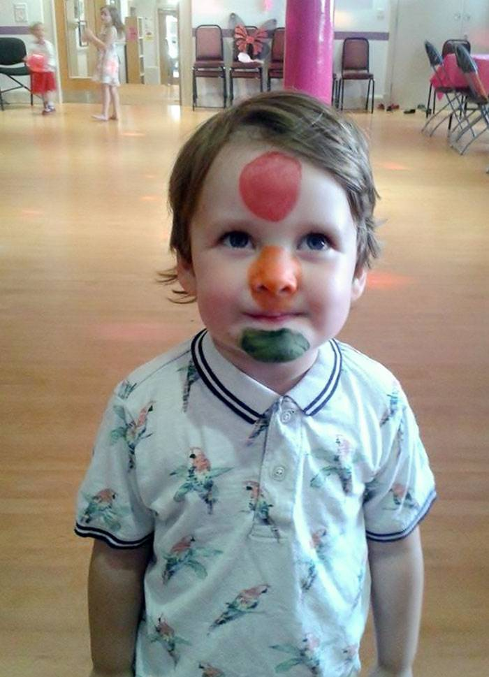 Little boy with a red, yellow, and green circle on his face; he is supposed to be a traffic light